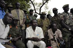 The leader of Uganda's Lord's Resistance Army rebels Joseph Kony (seated C), surrounded by his officers, addresses his first news conference in 20 years of rebellion in Nabanga, Sudan, August 1, 2006 where he called on a ceasefire with the government as a prelude to peace talks. BEST QUALITY AVAILABLE REUTERS/Adam Pletts (SUDAN) - RTR1G239