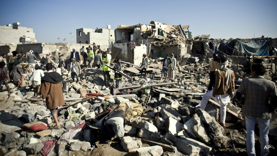 People search for survivors under the rubble of houses destroyed by Saudi airstrikes near Sanaa Airport, Yemen, Thursday, March 26, 2015. Saudi Arabia launched airstrikes Thursday targeting military installations in Yemen held by Shiite rebels who were taking over a key port city in the country's south and had driven the embattled president to flee by sea, security officials said.